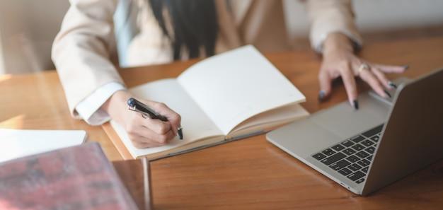 Vue rapprochée de la jeune femme d'affaires travaillant sur son projet et écrivant ses idées dans un cahier au bureau confortable