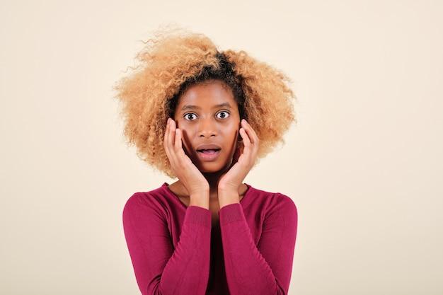 Vue rapprochée d'une jeune femme afro regardant avec une expression choquée devant la caméra en se tenant debout sur un fond isolé.