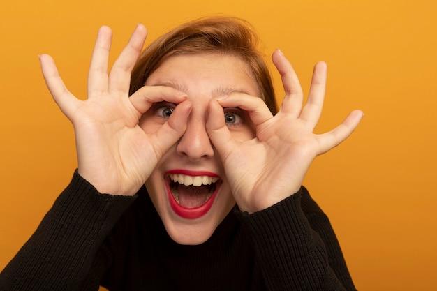 Vue rapprochée d'une jeune femme blonde joyeuse faisant un geste de regard en utilisant les mains comme des jumelles