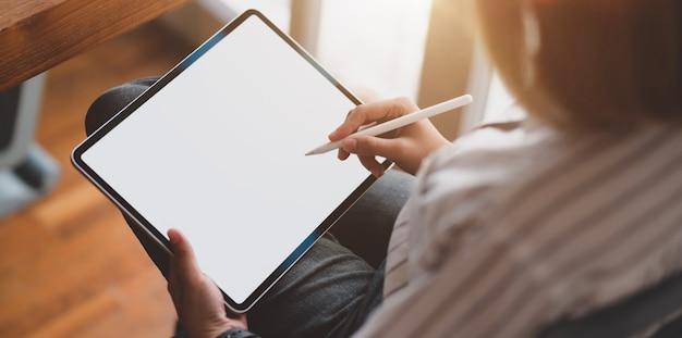 Vue rapprochée de la jeune femme designer travaillant sur une tablette à écran blanc