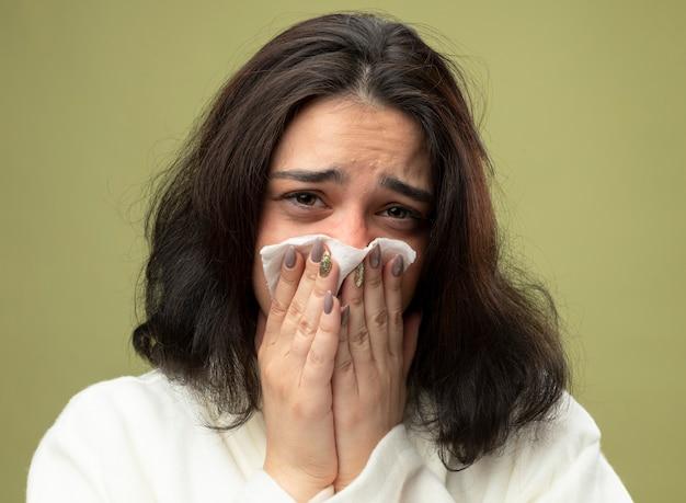 Vue rapprochée de la jeune femme malade portant une robe isolée sur un mur vert olive