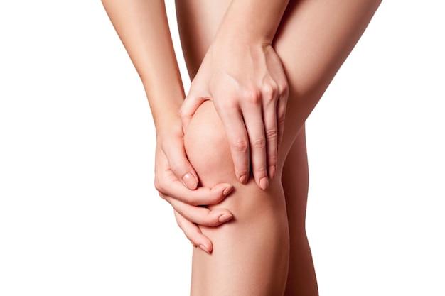 Vue rapprochée d'une jeune femme souffrant de douleurs au genou sur fond blanc.