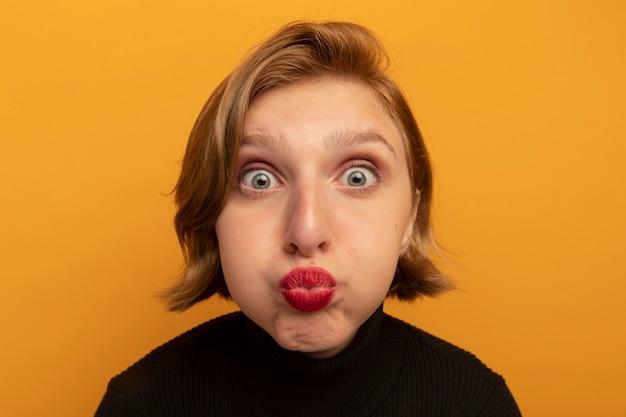 Vue rapprochée d'une jeune fille blonde impressionnée gonflant ses joues