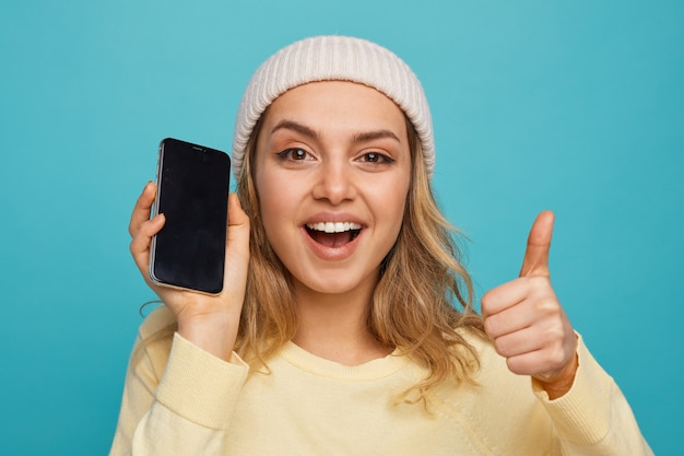 Vue rapprochée d'une jeune fille excitée portant un chapeau d'hiver tenant un téléphone mobile montrant le pouce vers le haut