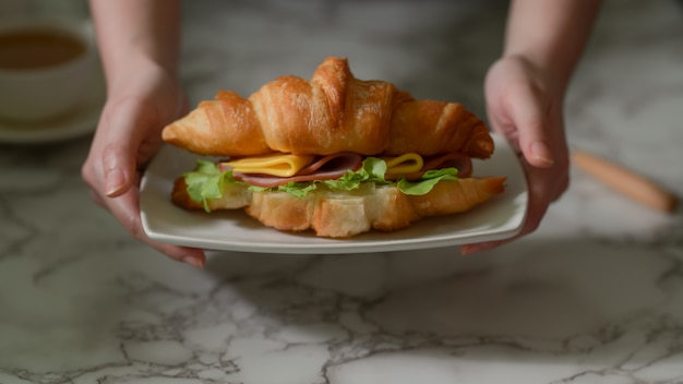 Vue rapprochée d'une jeune fille prenant son petit déjeuner, tenant une assiette de sandwich croissant