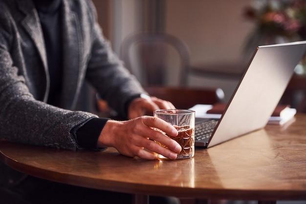 Vue rapprochée d'un jeune homme élégant en tenue de soirée assis dans un café avec son ordinateur portable et son verre d'alcool.