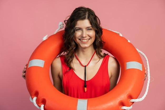 Vue rapprochée d'une jolie brune souriante avec une bouée de sauvetage autour du cou. jolie fille sur fond rose
