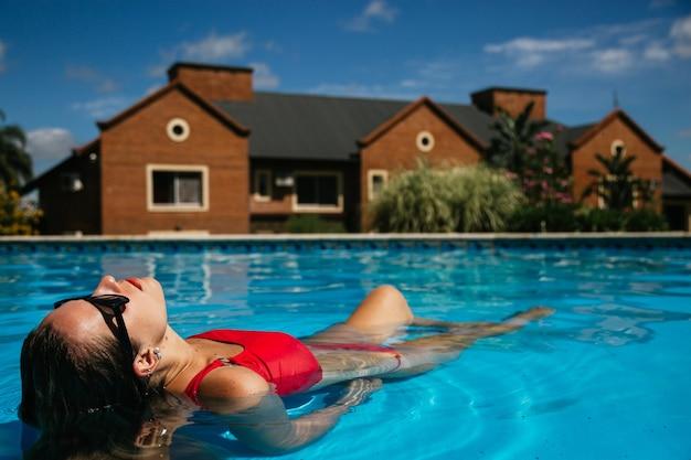 Vue rapprochée d'une jolie jeune femme se détendre au bord de la piscine de l'hôtel