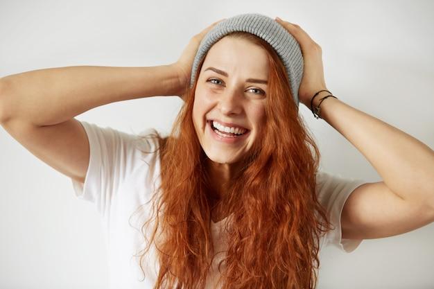 Vue rapprochée de la jolie jeune fille aux longs cheveux roux lâches, portant un t-shirt blanc et une casquette grise