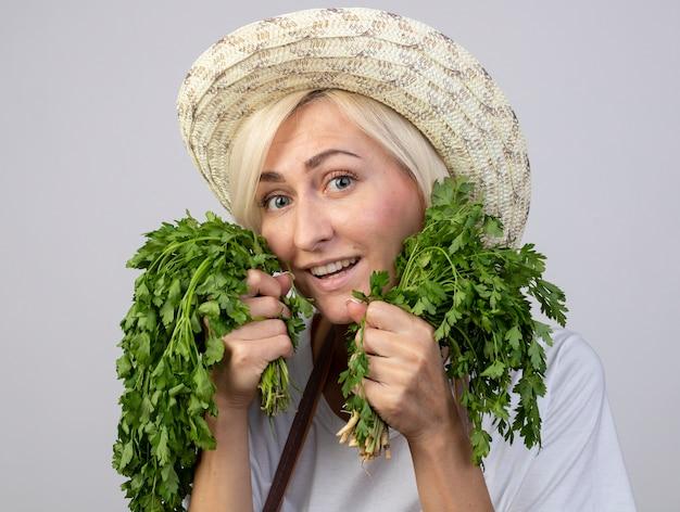 Vue rapprochée d'une joyeuse femme jardinière blonde d'âge moyen en uniforme portant un chapeau tenant deux bouquets de coriandre touchant le visage avec eux