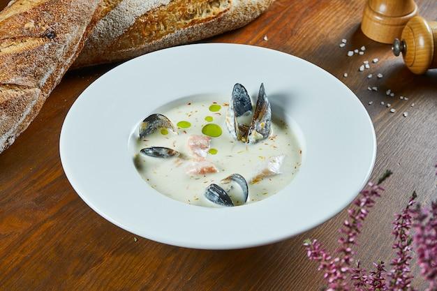 Vue rapprochée kalakeitto - soupe de crème de fruits de mer finlandaise traditionnelle avec de l'huile d'olive, des crevettes, des moules et du saumon dans un bol blanc sur une table en bois. nourriture savoureuse pour le déjeuner