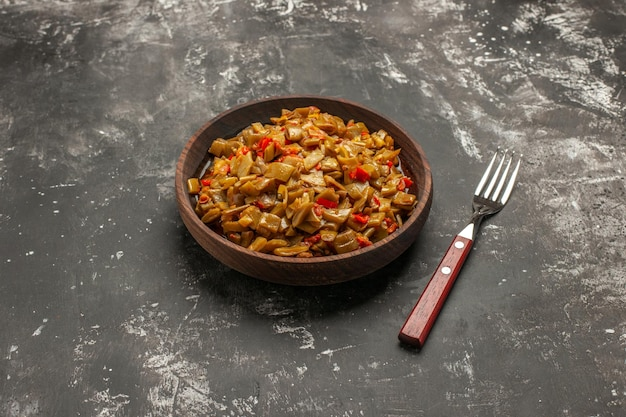 Vue rapprochée latérale assiette de haricots verts assiette en bois de haricots verts et tomates à côté de la fourchette sur la table sombre