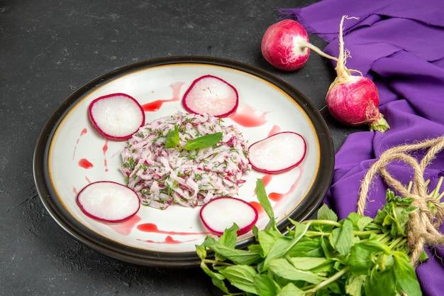 Vue rapprochée latérale d'une assiette de plat appétissant de radis et d'herbes en sauce et nappe violette