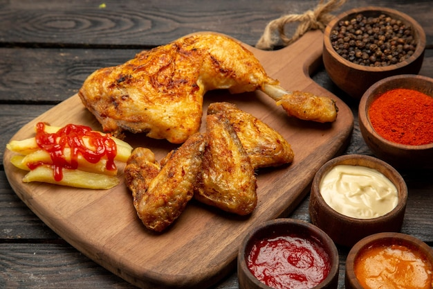 Vue rapprochée latérale des bols de poulet et d'épices de sauces et d'épices colorées et de cuisse et d'ailes de poulet et de frites sur la planche à découper