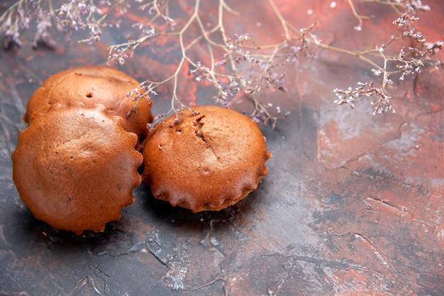 Vue rapprochée latérale des branches de cupcakes savoureux à côté des cupcakes savoureux sur la surface bleu-rouge
