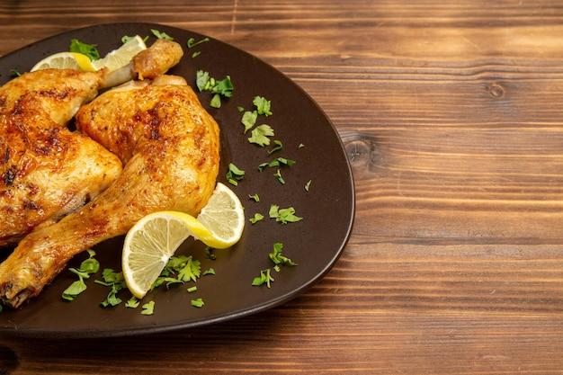 Vue rapprochée latérale du poulet et des herbes assiette brune de cuisses de poulet au citron et aux herbes sur le côté gauche de la table sombre