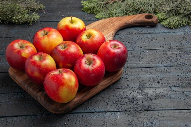 Vue rapprochée latérale des fruits à bord de neuf pommes jaune-rougeâtre sur une planche à découper en bois sur une table grise à côté des branches d'arbres