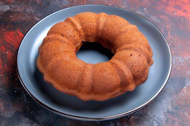 Vue rapprochée latérale un gâteau appétissant un gâteau appétissant sur la plaque bleue sur la table sombre