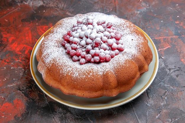 Vue rapprochée latérale d'un gâteau une assiette d'un gâteau avec des baies et du sucre en poudre