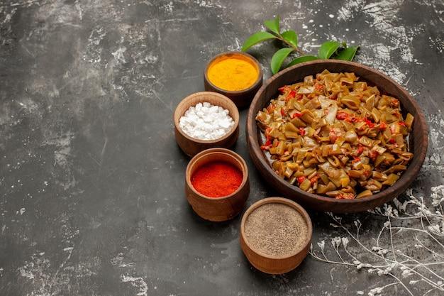 Vue rapprochée latérale des haricots verts aux épices avec des tomates à côté des bols de feuilles d'épices colorées et de branches d'arbres sur la table sombre