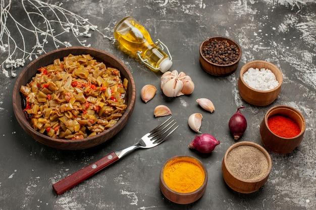 Vue rapprochée latérale des haricots verts et des épices des haricots verts dans le bol à côté de la fourchette des bols d'oignons à l'ail d'épices colorées et une bouteille d'huile sur la table