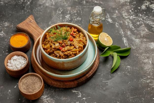 Vue rapprochée latérale des haricots verts avec des tomates assiette de haricots verts et trois épices à côté de la bouteille d'huile de citron et de feuilles