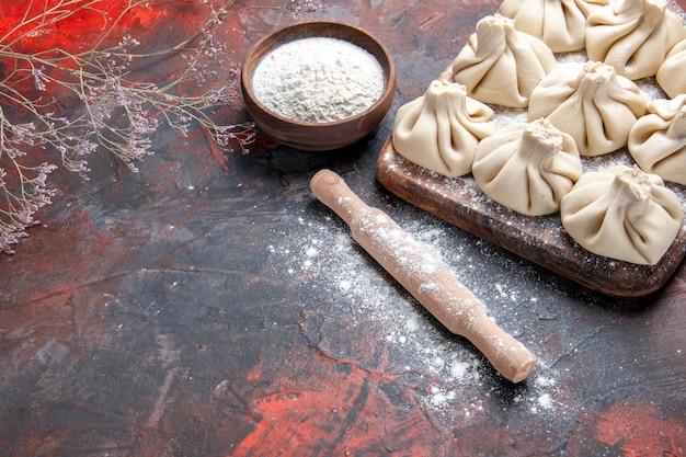 Vue rapprochée latérale khinkali khinkali sur le rouleau à pâtisserie de farine de branches d'arbres conseil