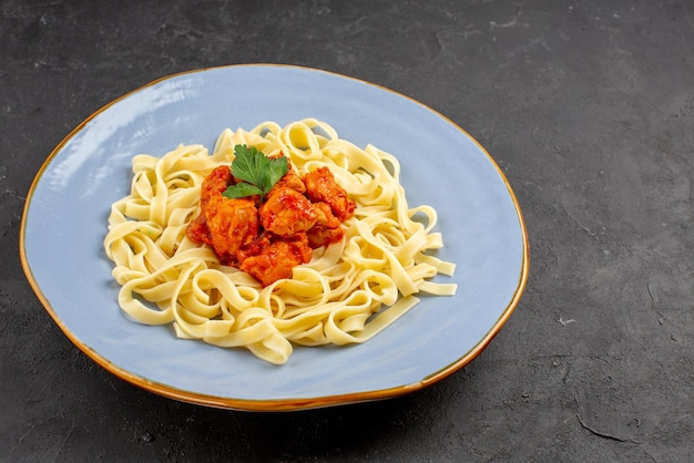 Vue rapprochée latérale de la nourriture appétissante des pâtes appétissantes avec de la sauce et de la viande dans la plaque bleue sur la table sombre