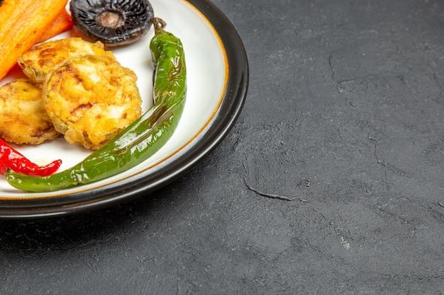 Vue rapprochée latérale de la plaque de légumes rôtis de l'appétissant champignons rôtis piments forts