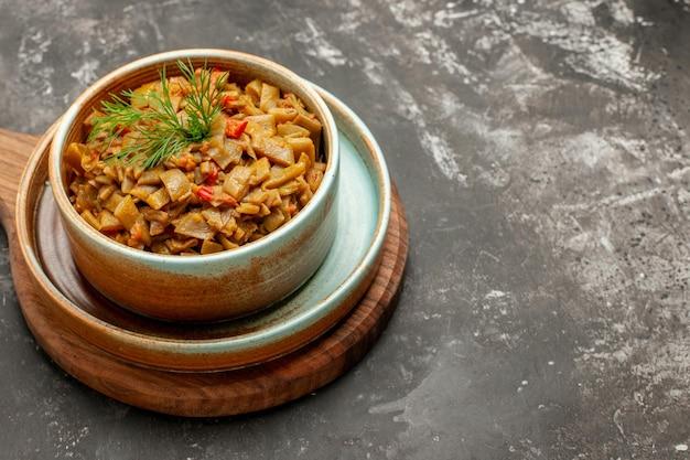 Vue rapprochée latérale plat appétissant plat appétissant de haricots verts aux tomates sur la planche à découper sur la table sombre