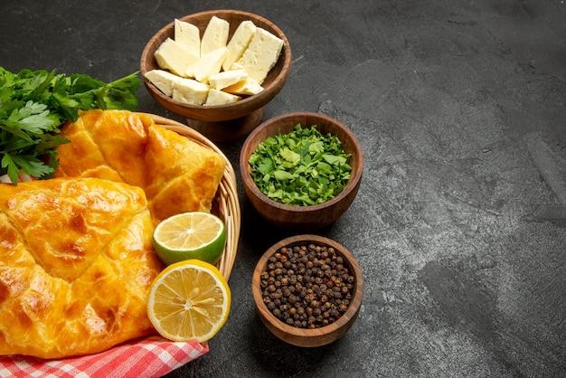 Vue rapprochée latérale plat dans le panier panier en bois de tartes aux herbes de citron et nappe rose-blanc et bols d'herbes de poivre noir et de fromage sur la table
