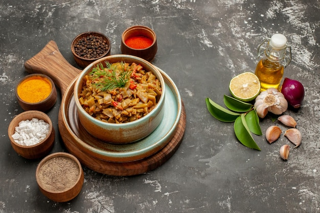 Vue rapprochée latérale plat et épices cinq bols d'épices assiette de tomates et haricots verts à côté de la bouteille de feuilles d'huile et de citron