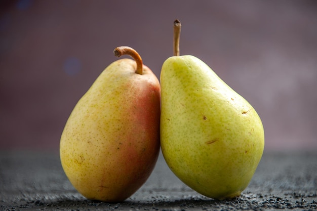 Vue rapprochée latérale des poires sur la table deux poires mûres vert-jaune-rouge sur la table en bois