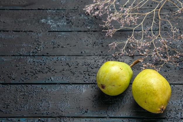 Vue rapprochée latérale des poires sur la table des poires vertes à côté des branches d'arbres sur le côté droit de la table grise en bois