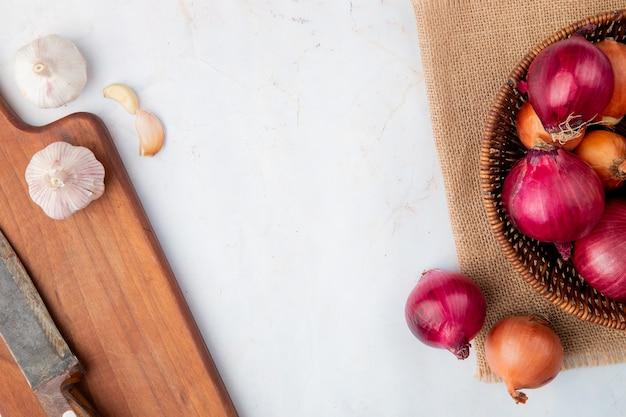 Vue rapprochée de légumes comme l'ail et l'oignon sur une planche à découper et un sac sur fond blanc avec copie espace