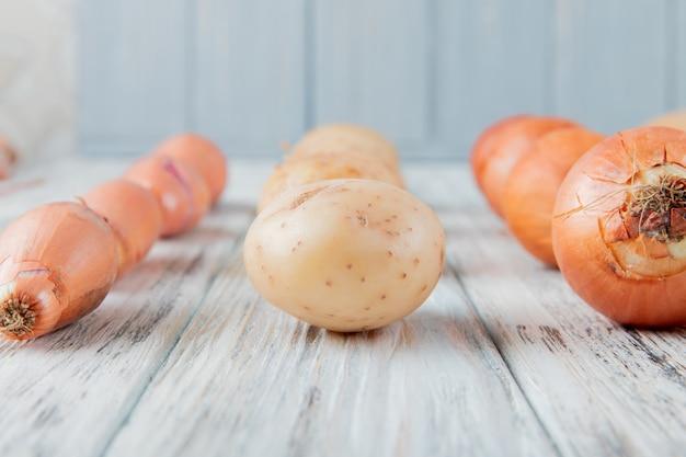 Vue rapprochée de légumes comme l'oignon et la pomme de terre sur la surface en bois et l'arrière-plan avec copie espace