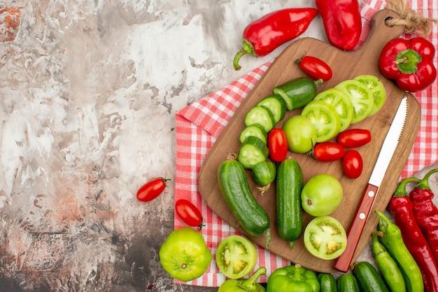 Vue rapprochée de légumes frais entiers et hachés sur une planche à découper en bois