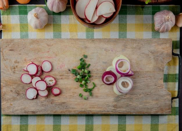Vue rapprochée de légumes en tranches comme oignon échalote de radis sur une planche à découper sur fond de tissu