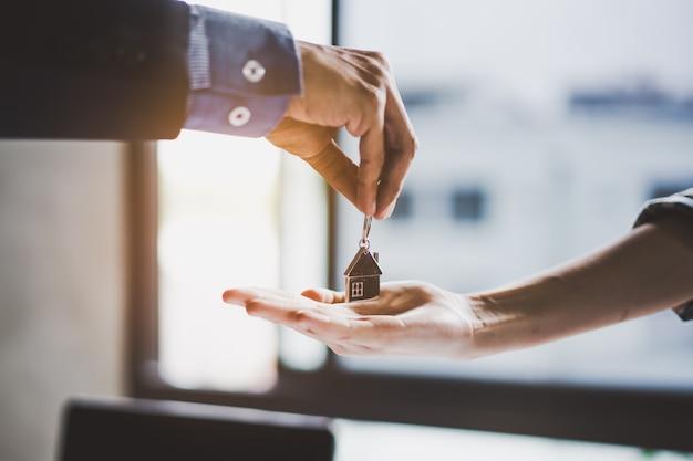 Vue rapprochée de la main d'un agent immobilier / propriétaire donnant une maison clé à l'acheteur / locataire.