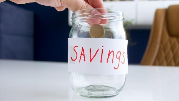 Vue rapprochée de la main féminine mettant une pièce dans un bocal en verre pour économiser de l'argent.