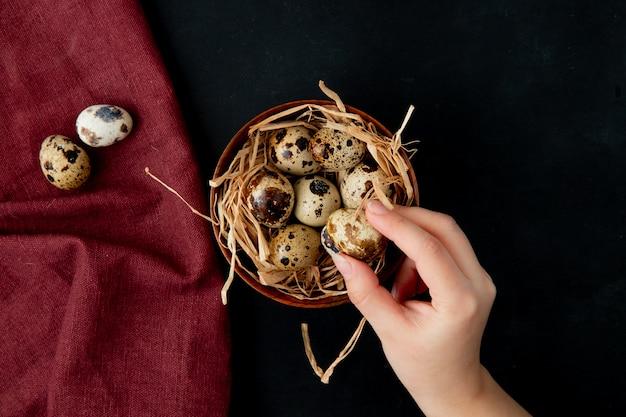 Vue rapprochée de la main de femme tenant l'oeuf avec un bol d'oeufs avec nid sur bourgogne et noir