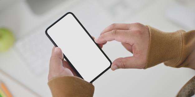 Vue rapprochée de la main de l'homme sur un smartphone à écran blanc