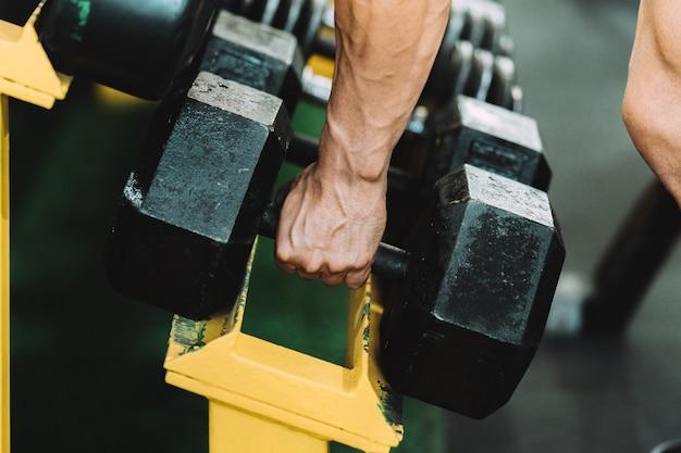 Vue rapprochée d'une main masculine ramassant un haltère d'un rack dans une salle de sport