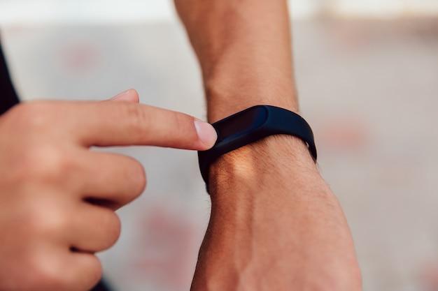 Vue rapprochée de la main masculine tout en vérifiant un cardio et le temps après la course