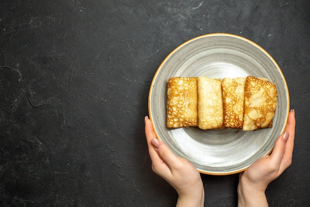 Vue rapprochée de la main tenant de délicieuses crêpes fourrées à la viande sur une plaque blanche sur fond noir