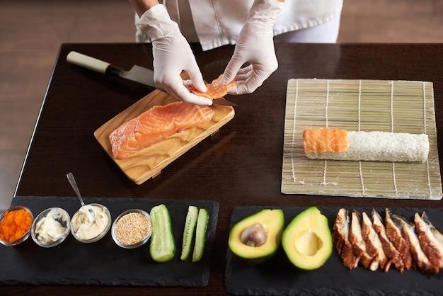 Vue rapprochée des mains du chef préparant la nourriture japonaise