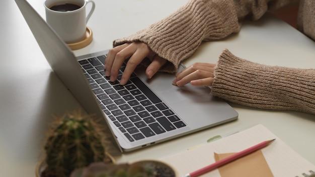 Vue rapprochée des mains féminines en tapant sur le clavier d'ordinateur portable sur la table de travail dans la salle de bureau à domicile