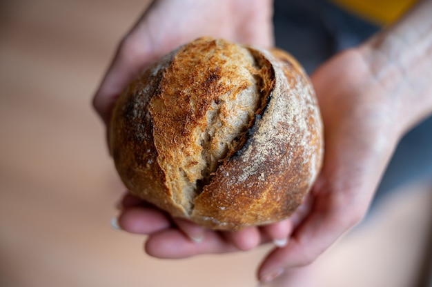 Vue rapprochée des mains féminines tenant un délicieux pain doré.