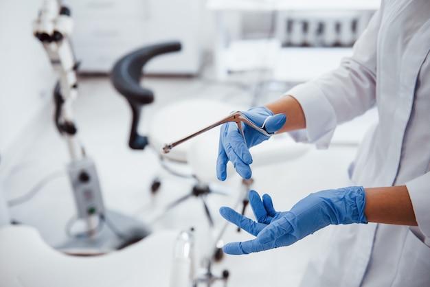 Vue rapprochée des mains d'une femme médecin qui détient l'instrument rétracteur.