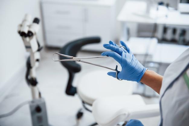 Vue rapprochée des mains d'une femme médecin qui détient une pince.